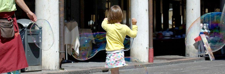 Bambina che gioca con bolle di sapone giganti. Famille de la rue.
